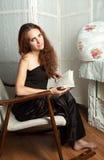 Porträt der attraktiven Jugendlichen im Schaukelstuhl mit Buch Lizenzfreie Stockfotos