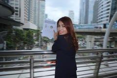 Porträt der attraktiven jungen asiatischen Geschäftsfrau, die Diagramme oder Schreibarbeit im äußeren Büro hält lizenzfreie stockfotografie