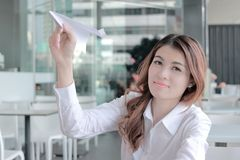 Porträt der attraktiven jungen asiatischen Geschäftsfrau, die Papierfläche in ihren Händen im Büro hält Vergrößerungsglas, das au Stockfotos