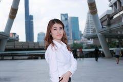 Porträt der attraktiven jungen asiatischen Geschäftsfraustellung am Bürgersteig und des Betrachtens der Kamera Denken und durchda stockbild