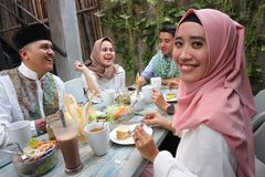 Porträt der attraktiven jungen moslemischen Frau, die Kamera während andere genießende Mahlzeit betrachtet stockfotos