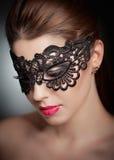 Porträt der attraktiven sinnlichen jungen Frau mit Maske. Junge attraktive Brunettedame, die auf grauem Hintergrund im Studio aufw Lizenzfreie Stockbilder