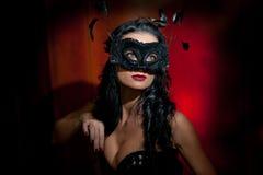 Porträt der attraktiven sinnlichen jungen Frau mit Maske, zuhause Sinnliche Brunettedame, die provozierend auf rotem Hintergrund  Lizenzfreies Stockbild
