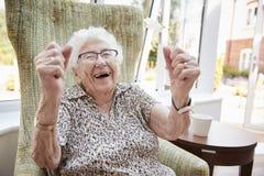Porträt der aufgeregten älteren Frau, die im Stuhl im Aufenthaltsraum des Ruhesitzes sitzt stockfoto