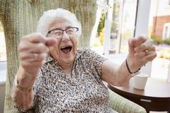 Porträt der aufgeregten älteren Frau, die im Stuhl im Aufenthaltsraum des Ruhesitzes sitzt lizenzfreie stockfotos