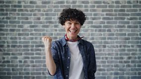 Porträt der aufgeregten jungen Frau, welche die Fäuste feiern Erfolg und Glück anhebt stock footage