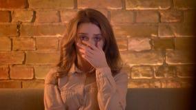 Porträt der aufmerksamen jungen Jugendlichen, die fernsieht und ihre Hand hält, um in der Furcht gegenüberzustellen sitzt im Wohn stock footage
