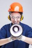 Porträt der ausdrucksvollen kaukasischen Frau mit dem Lautsprecher-Horn, das im Hardhat schreit Stockbilder