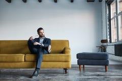 Porträt der bärtigen und hübschen Klage des Geschäftsmannes in Mode, die auf Sofa in einem modernen Büro stillsteht und herein sc lizenzfreie stockfotos