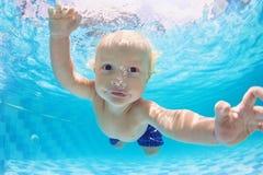Porträt der Babyschwimmens und -tauchens Unterwasser im Pool Lizenzfreie Stockfotos