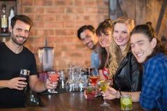 Porträt der Barmixerumhüllung trinkt zu den glücklichen Kunden stockbilder
