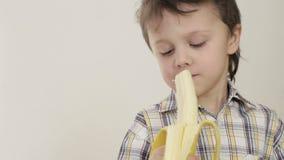 Porträt der beißenden Banane des kleinen Jungen stock video