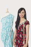 Porträt der bereitstehenden Attrappe des glücklichen indischen weiblichen Modedesigners drapierte in einem Sari lizenzfreie stockfotografie
