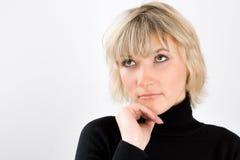 Porträt der blonden Frau in einem schwarzen Golf Stockbild