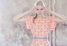 Porträt der blonden Frau im rosa Kleid nahe hellgrauer Wand Lizenzfreies Stockfoto