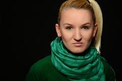 Porträt der blonden Frau Sie auf schwarzem backgound betrachtend lizenzfreies stockbild