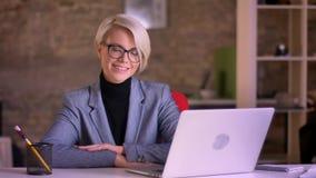 Porträt der blonden kurzhaarigen Geschäftsfrau in den Gläsern und in den Händen kreuzte auf Tabelle lächelnd in Kamera im Büro stock video