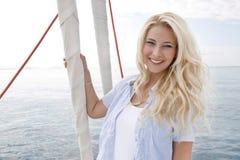 Porträt der blonden schönen jungen Frau auf Segelboot. Lizenzfreie Stockfotos