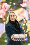 Porträt der Blondine im Mantel mit Geschenkbox auf Hintergrund des Weihnachtsbaums stockfotos