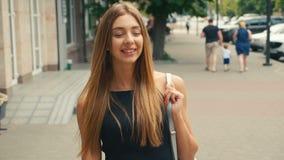 Porträt der braunen behaarten jungen Frau, die Kamera steadicam Schuss betrachtet Porträtschönheit auf städtischer Stadtstraße stock video