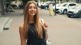 Porträt der braunen behaarten jungen Frau, die Kamera steadicam Schuss betrachtet Porträtschönheit auf städtischer Stadtstraße stock footage
