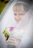 Porträt der Braut mit Blumenstrauß im langen Schleier stockfotografie