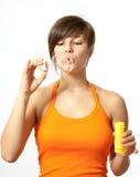 Porträt der durchbrennenSeifenblasen einer jungen Frau Stockfotografie