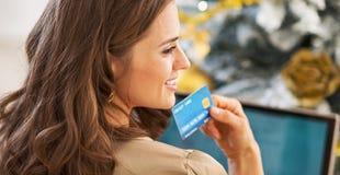 Porträt der durchdachten jungen Frau mit Kreditkarte und Laptop Lizenzfreie Stockbilder