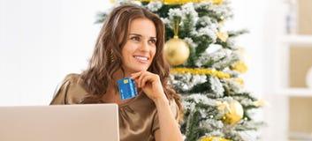Porträt der durchdachten jungen Frau mit Kreditkarte unter Verwendung des Laptops Lizenzfreie Stockfotografie