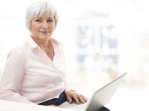 Lächelnde ältere Frau, die an Laptop arbeitet Stockbild