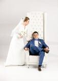 Porträt der eleganten Braut den Bräutigam umarmend, der auf Stuhl sitzt lizenzfreie stockfotografie