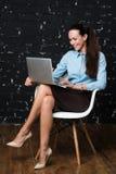 Porträt der eleganten gekleideten Brünettefrau, die in der Dachbodenwohnung sitzt und an tragbarem Laptop arbeitet Stockfotos