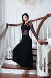 Porträt der Eleganzfrau auf Schritten Schwarzes Kleid Lizenzfreie Stockfotografie