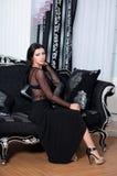 Porträt der Eleganzfrau im schwarzen Kleid auf Sofa Stockbild