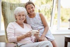 Porträt der Enkelin-Besuchsgroßmutter im Aufenthaltsraum des Ruhesitzes stockfotos