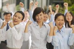 Porträt der enthusiastischen und aufgeregten Gruppe Geschäftsleute, die mit den Fäusten oben zujubeln Stockbild