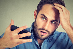 Porträt, der entsetzte Manngefühlskopf, überrascht ist er verlierendes Haar Stockfotografie