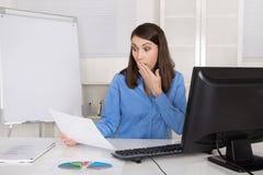 Porträt der entsetzten und überraschten Geschäftsfrau, die am Schreibtisch sitzt Stockbild