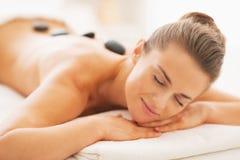 Porträt der entspannten jungen Frau, die Warmsteinmassage empfängt Stockfotos