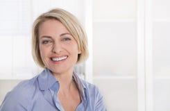 Porträt der erfüllten älteren Geschäftsfrau im Blau im Büro. Lizenzfreies Stockfoto