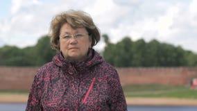 Porträt der ernsten erwachsenen Frau alterte 60s draußen stock footage