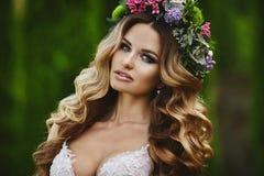 Porträt der erstaunlichen Schönheit, blondes vorbildliches Mädchen mit Blumenkranz auf ihrem Kopf Stockfotos