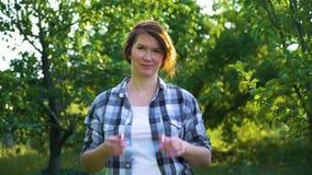 Porträt der erwachsenen Frau im überprüften Hemd, das auf Schutzgläser in Garten sich setzt stock footage