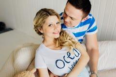 Porträt der Erwartung von den Paaren, die glücklich über Kamera, Baby im Bauch zusammen umfassend lachen Stockbilder