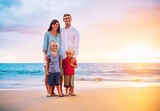 Porträt der Familie auf dem Strand bei Sonnenuntergang Stockbild