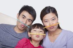 Porträt der Familie ein Gesicht mit Trinkhalmen machend Stockbilder