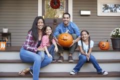 Porträt der Familie Halloween-Kürbis auf Haus-Schritten schnitzend lizenzfreie stockfotografie