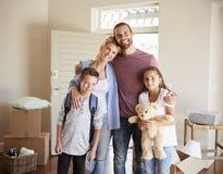 Porträt der Familie im Aufenthaltsraum des neuen Hauses an beweglichem Tag lizenzfreie stockbilder