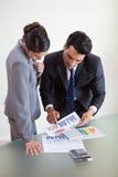 Porträt der fokussierten Verkaufspersonen, die Statistiken studieren Stockbilder