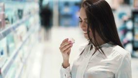 Porträt der Frau in den Kosmetik kaufen wählt Gesichtscreme, schnüffelt sie und Lachen stock video